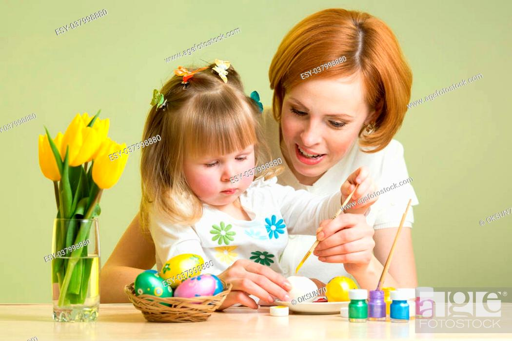 Imagen: happy mother teaches child daughter to paint easter eggs.