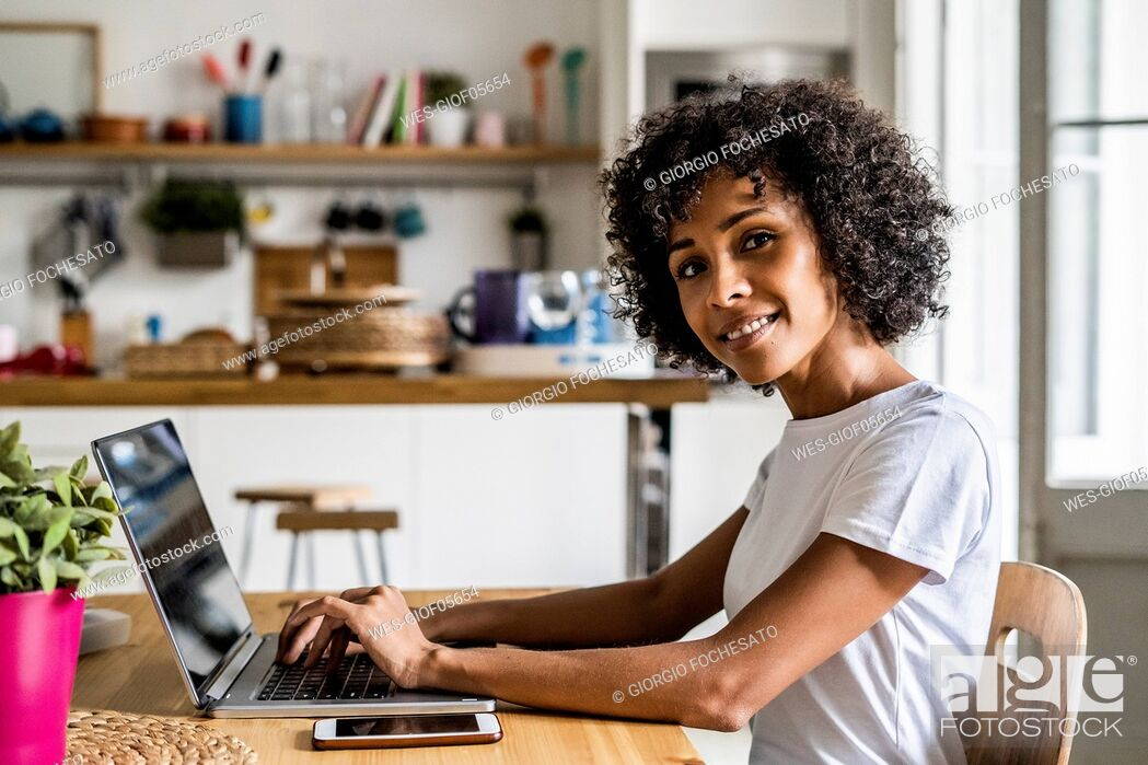Stock Photo: Portrait of smiling woman using laptop at table at home.