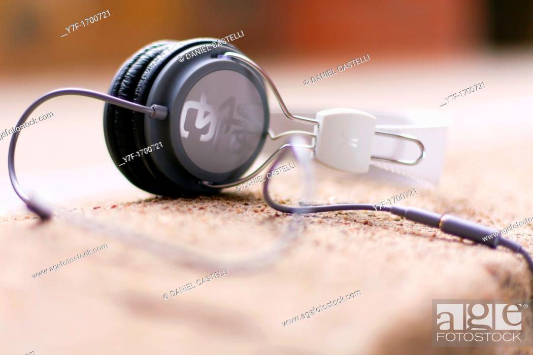 Stock Photo: Headphones lying on a wall.