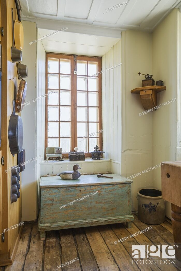 Stock Photo: Kitchen corner wall with tin and copper cooking pots and pans and faded turquoise painted antique wooden storage chest inside an old 1835 fieldstone house.