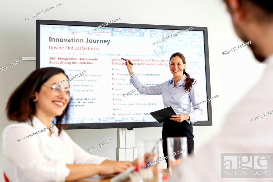 Stock Photo: Smiling businesswoman leading a presentation.