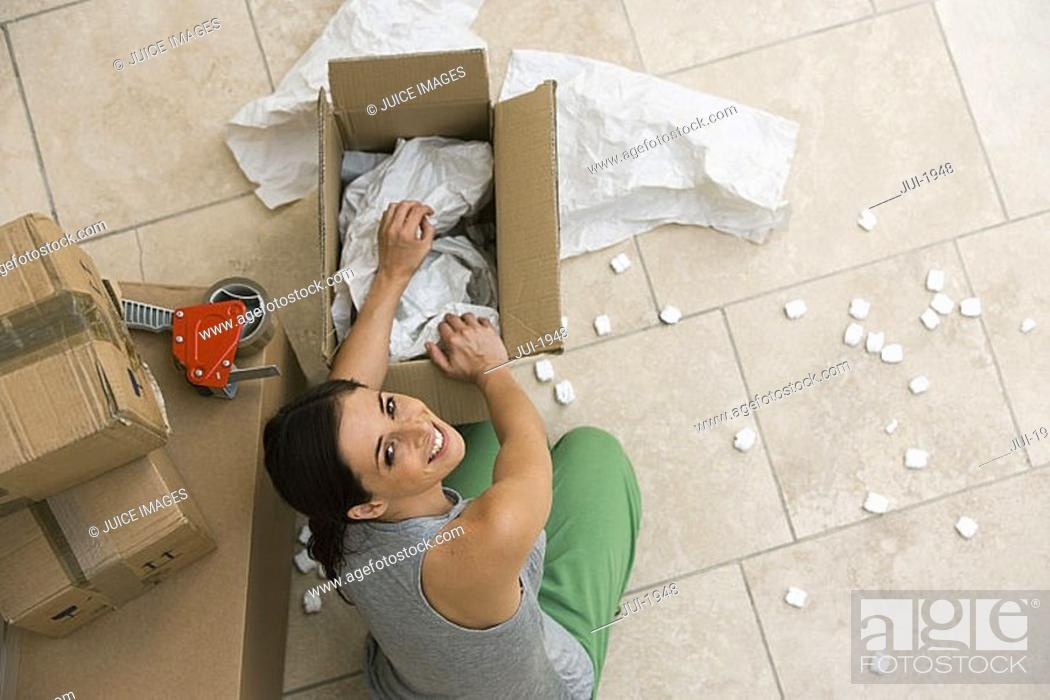 Stock Photo: Woman sitting on floor, packing box with paper and foam, smiling, portrait, overhead view.