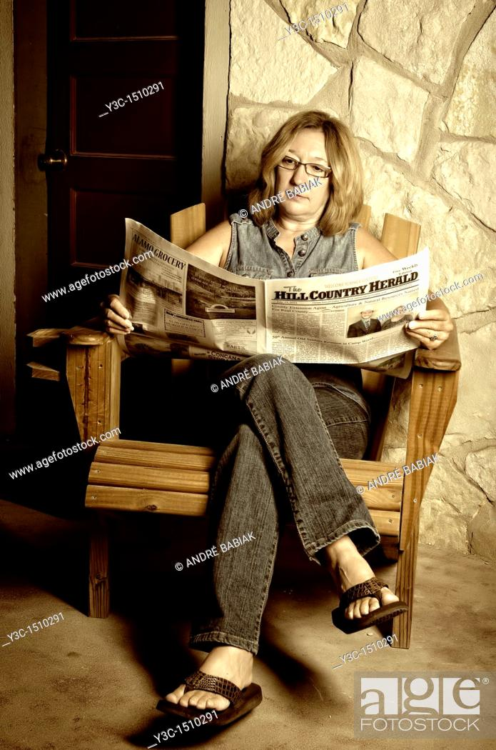 Stock Photo: Woman reading newspaper.