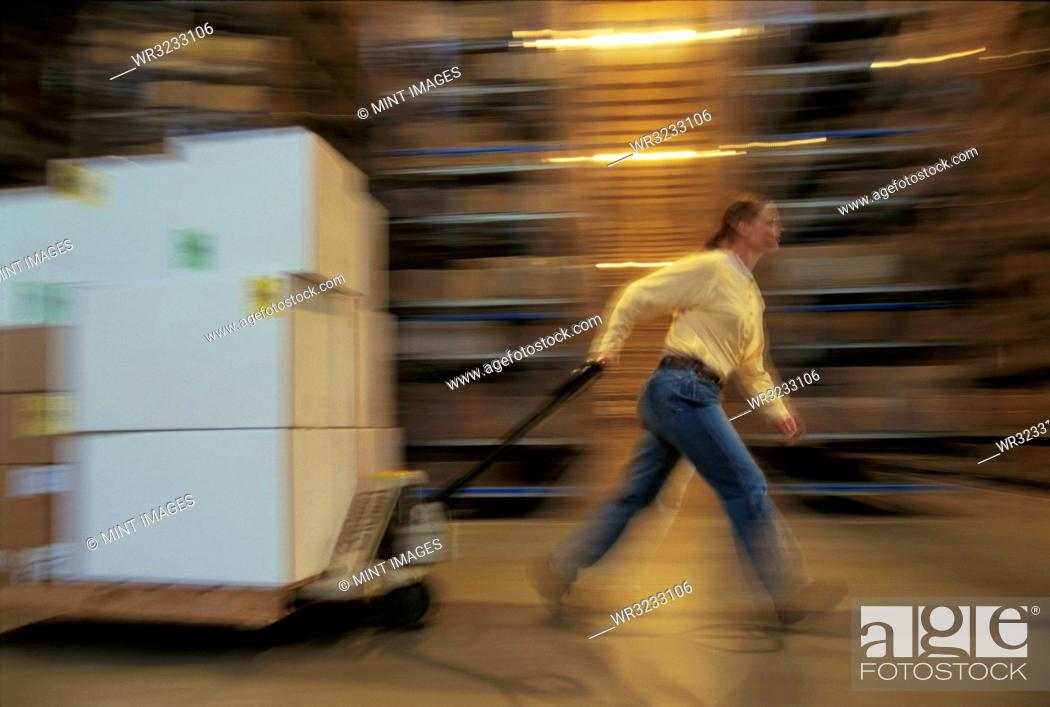Stock Photo: Warehouse employee moving a pallet of products in cardboard boxes in a large distribution warehouse.