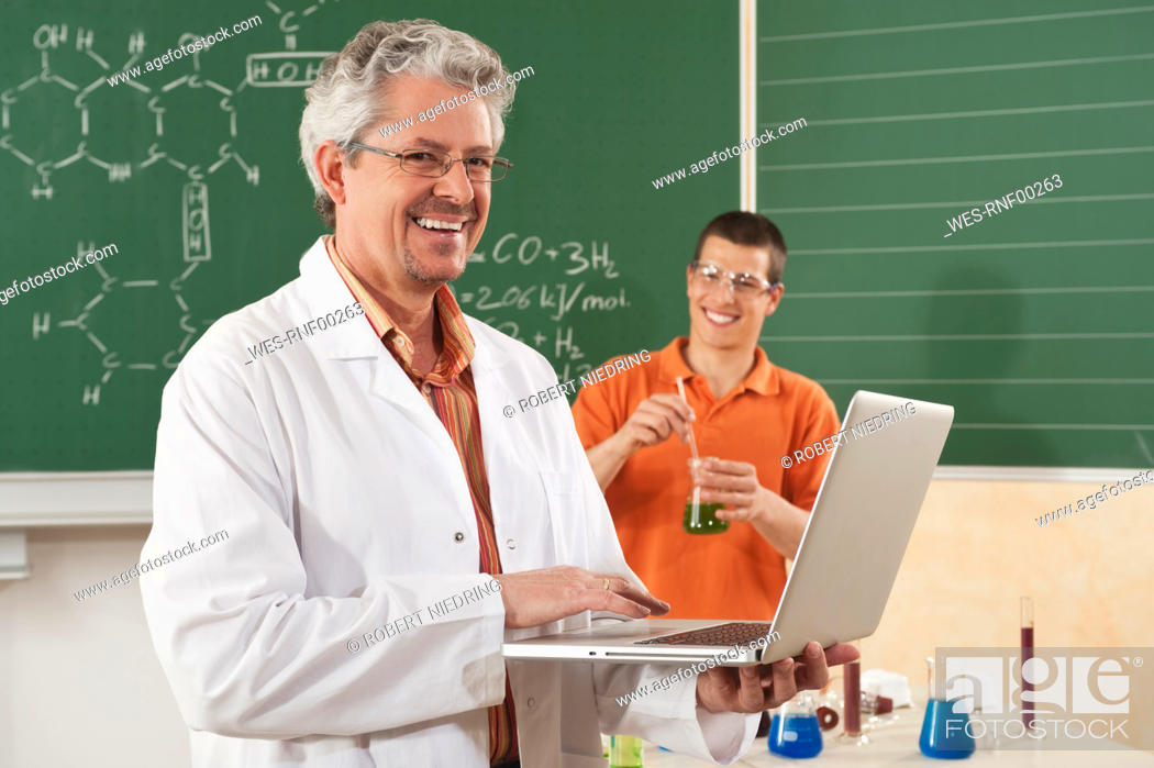 Stock Photo: Germany, Emmering, Man using laptop with young man doing experiment in background.