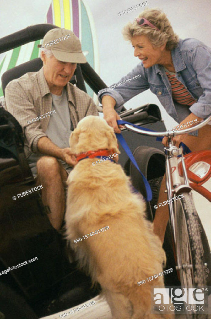 Stock Photo: Senior couple on a jeep and bicycle with their dog.