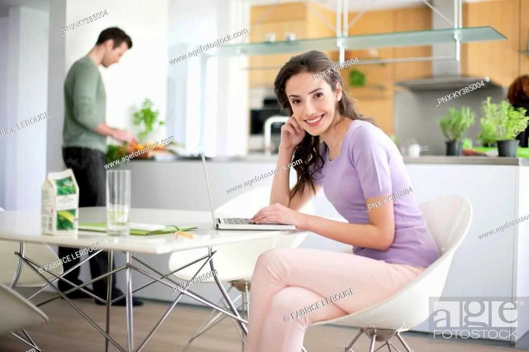 Stock Photo: Woman using a laptop with her husband preparing food in the background.