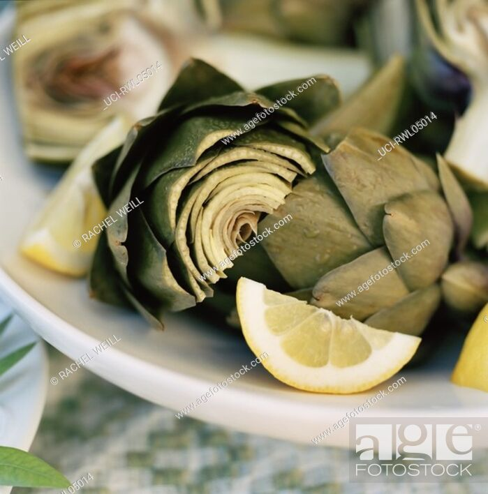 Stock Photo: Close up of artichoke hearts with lemon wedges.