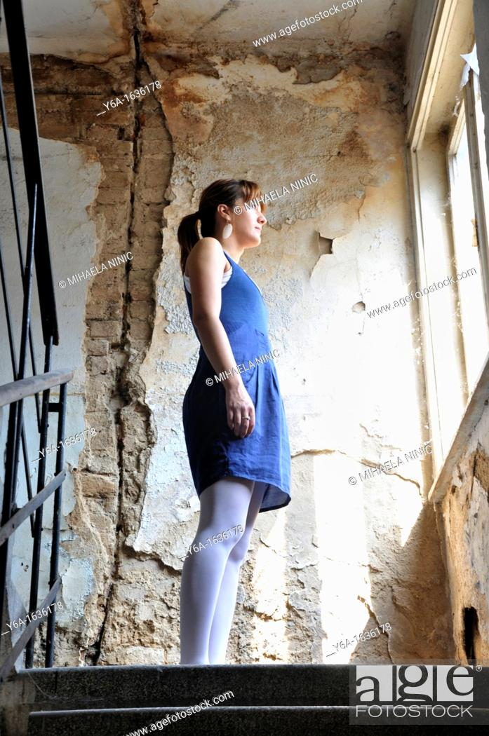 Stock Photo: Young woman standing in ruined corridor looking through window.