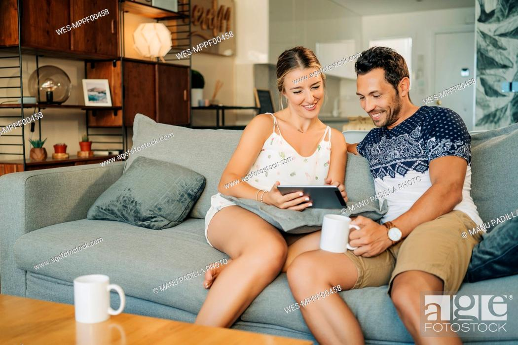 Stock Photo: Happy relaxed couple sitting on couch in living room sharing a tablet.