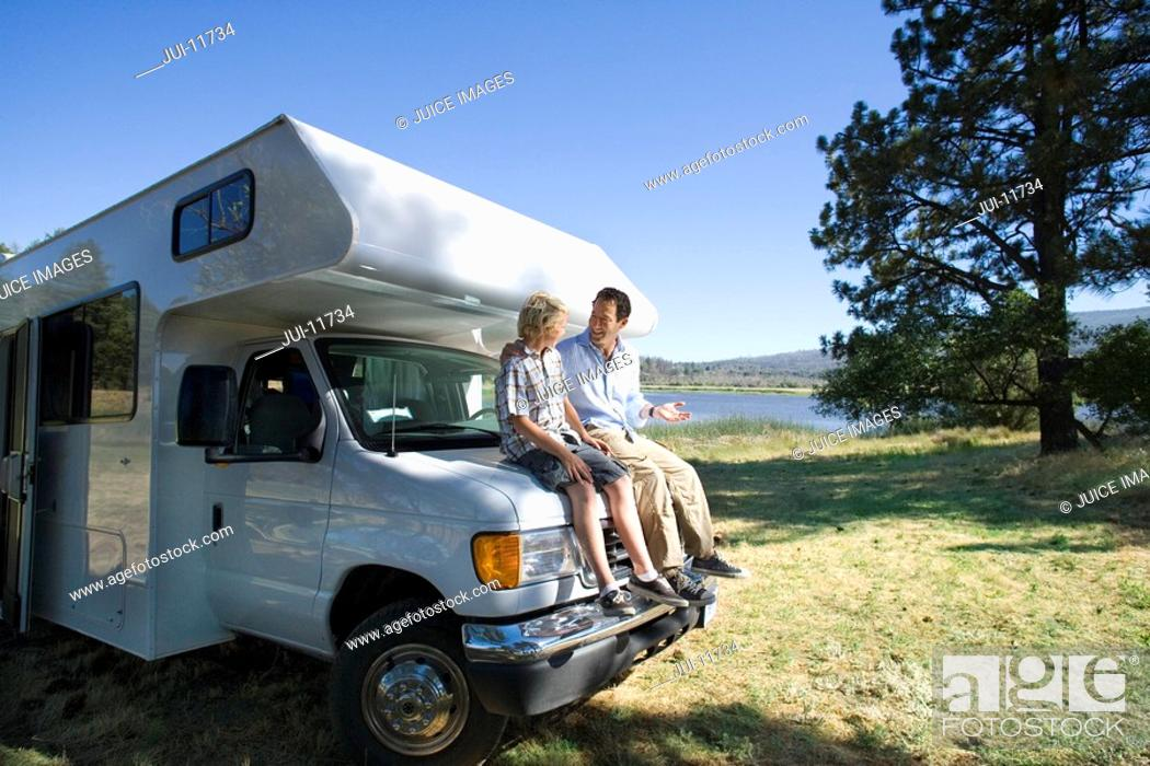 Stock Photo: Father and son 10-12 smiling at each other on front of motor home by lake.