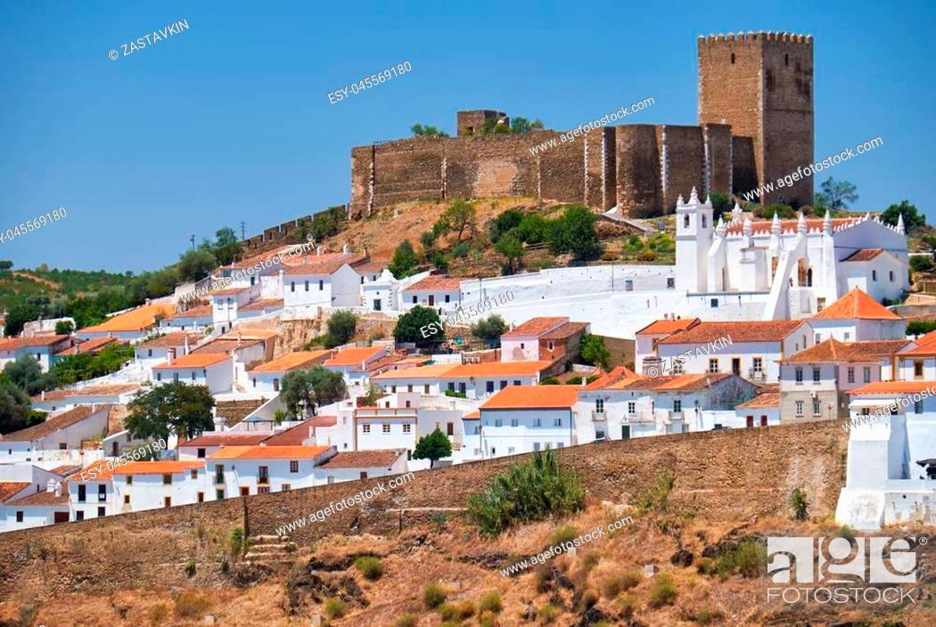 Imagen: The mediaeval castle on the top of the hill surrounded by residential Alentejo country-style houses inside the old city walls of Mertola.