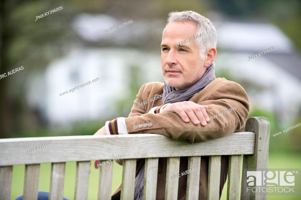 Stock Photo: Man sitting on a bench and thinking in a park.