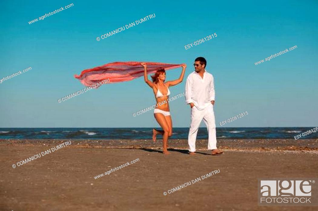Stock Photo: happy, young couple walking along the seashore.