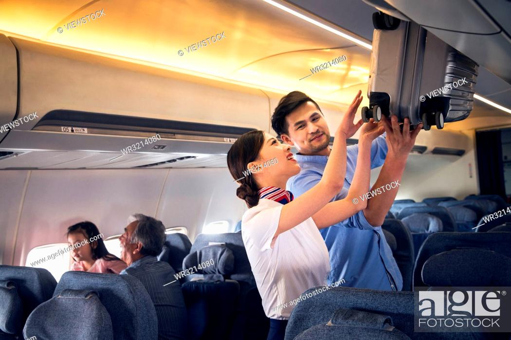 Stock Photo: Flight attendants and passengers on the plane.
