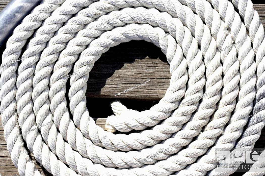 Stock Photo: Coiled rope on jetty, close-up.
