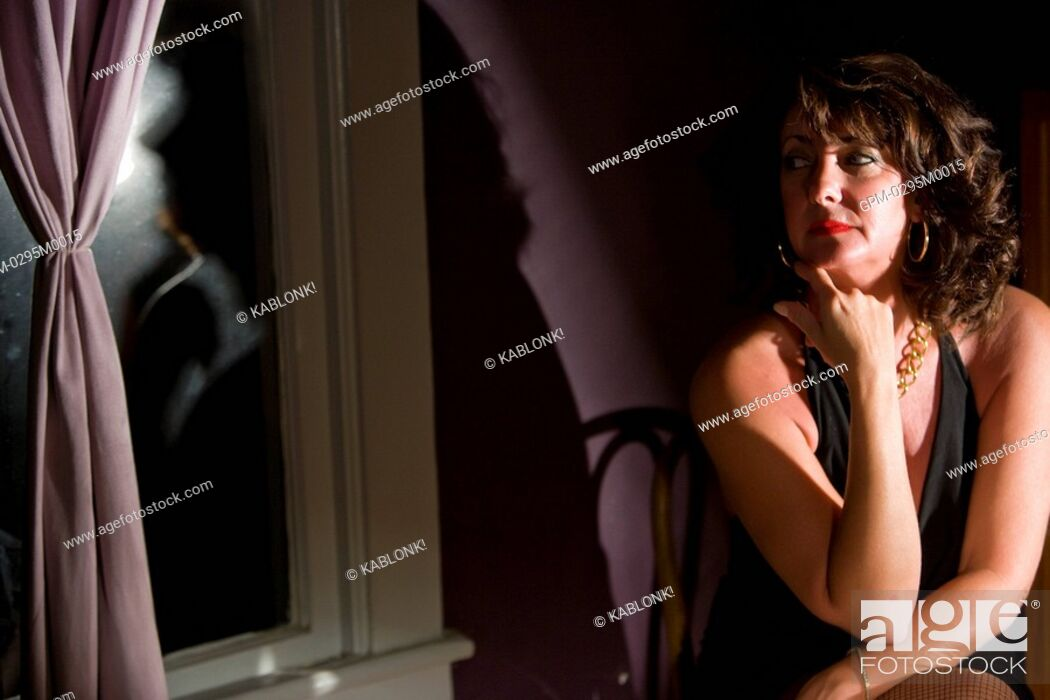 Imagen: Portrait of thoughtful mid adult woman sitting in house looking out window.