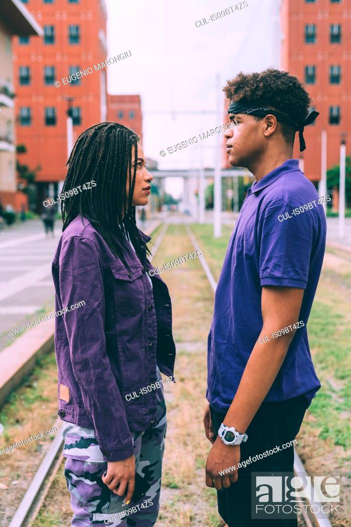 Stock Photo: Brother and sister face to face on tram tracks, Milan, Italy.