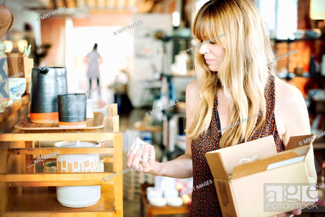 Imagen: Woman in a shop, holding a small cardboard box with merchandise.