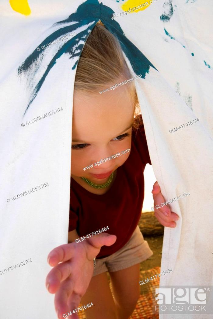 Stock Photo: Baby girl peeking out from a tent.