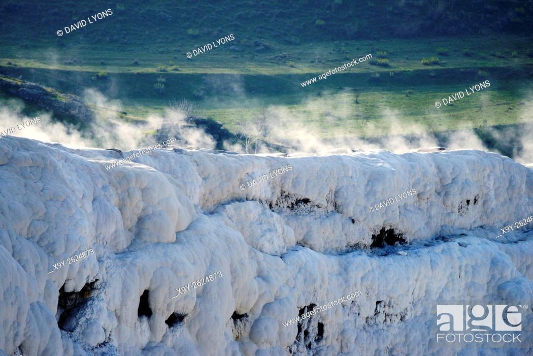 Stock Photo: Pamukkale, Denizli, Turkey. Hot spring steam rises from limestone wall above travertine calcium carbonate terrace pool deposits.