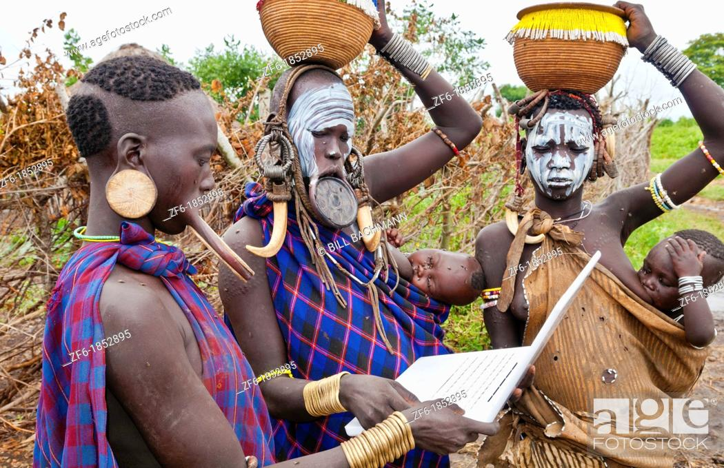 Stock Photo: Jinka Ethiopia Africa village Lower Omo Valley Mago National Park wild tribe Mursi women with clay pots in their lips working on modern computer email in tribal.