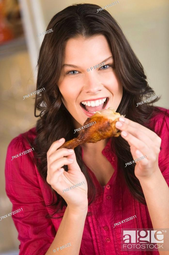 Stock Photo: Woman eating chicken.