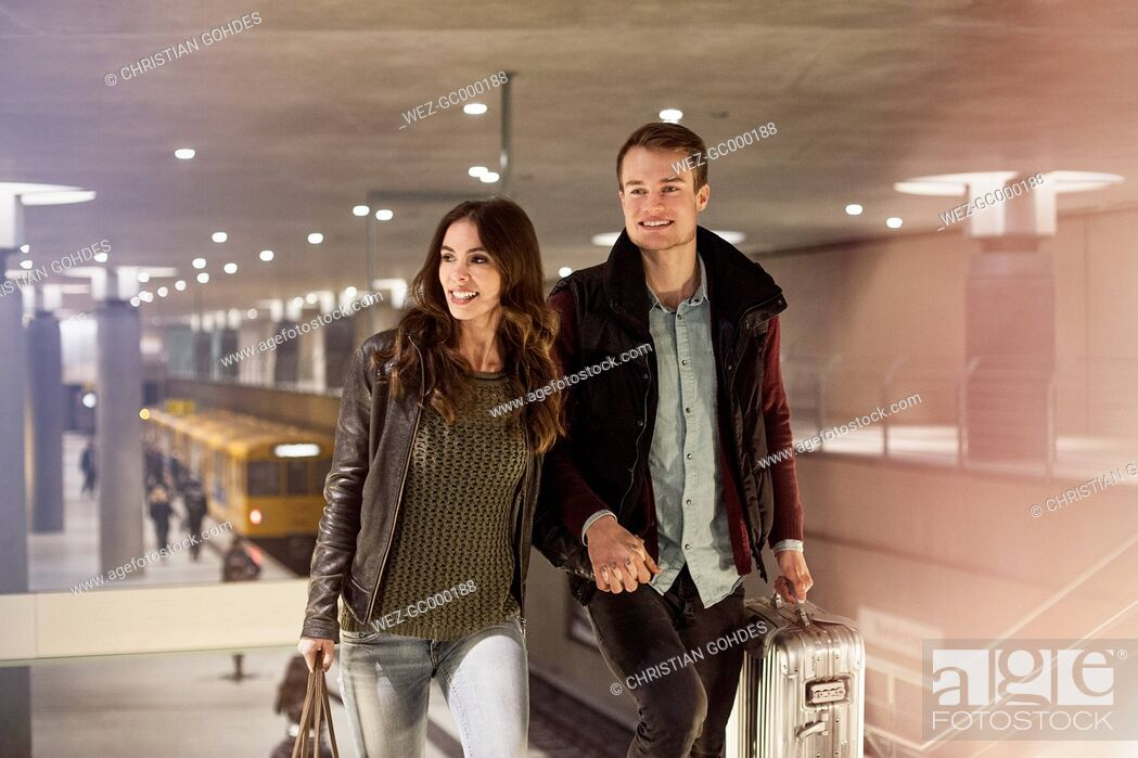 Stock Photo: Germany, Berlin, smiling couple leaving underground station.