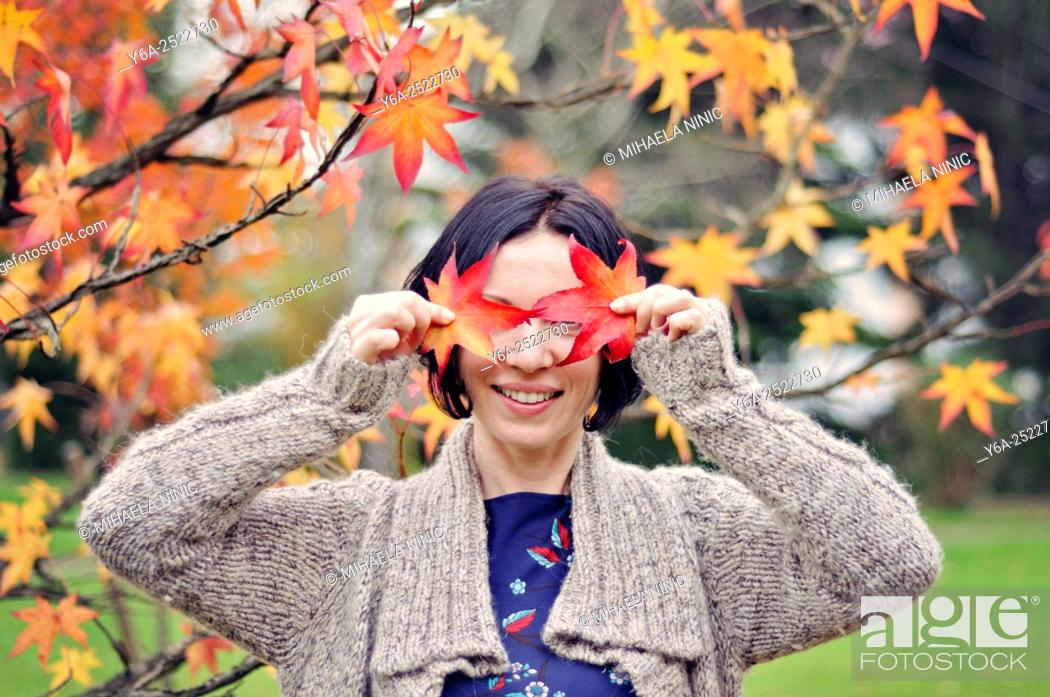 Stock Photo: Smiling mid adult woman holding leaf close to her face, autumn.