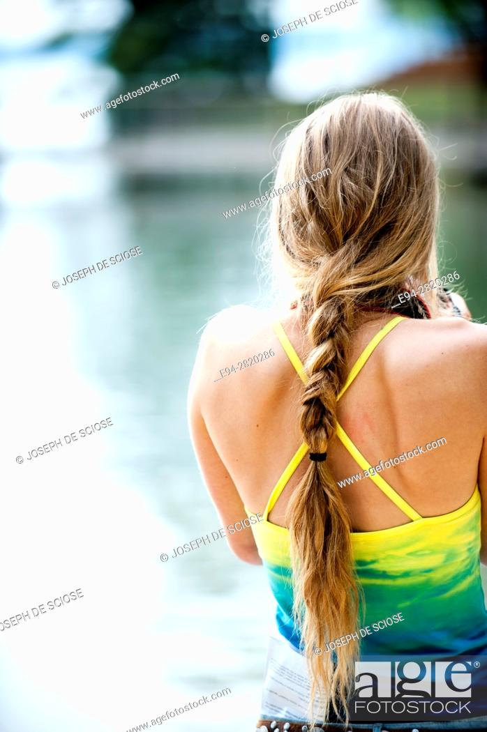 Photo de stock: Back view of a 20 year old blond woman with bare shoulders with her hair in a pony tail in an outdoor setting in the summer.