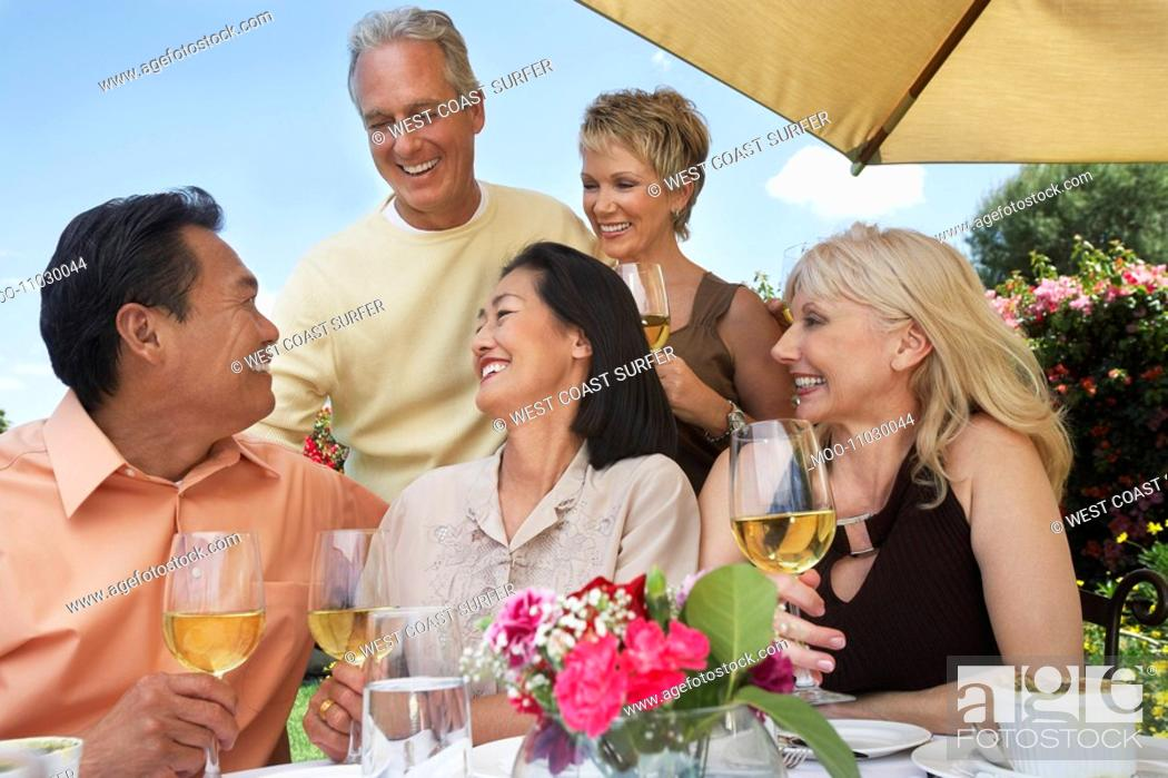 Stock Photo: Five friends at table drinking wine at garden party.