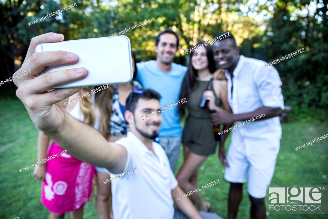 Stock Photo: Friends taking a selfie in a garden during a summer party.