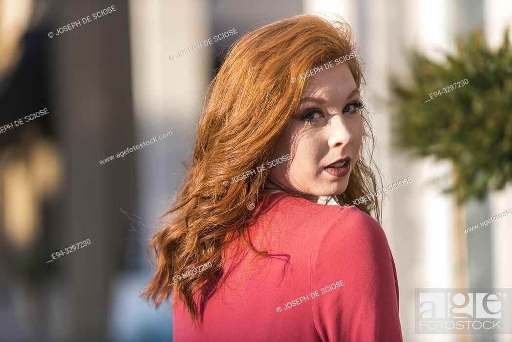 Stock Photo: Portrait of a 25 year old redheaded woman in an urban setting.