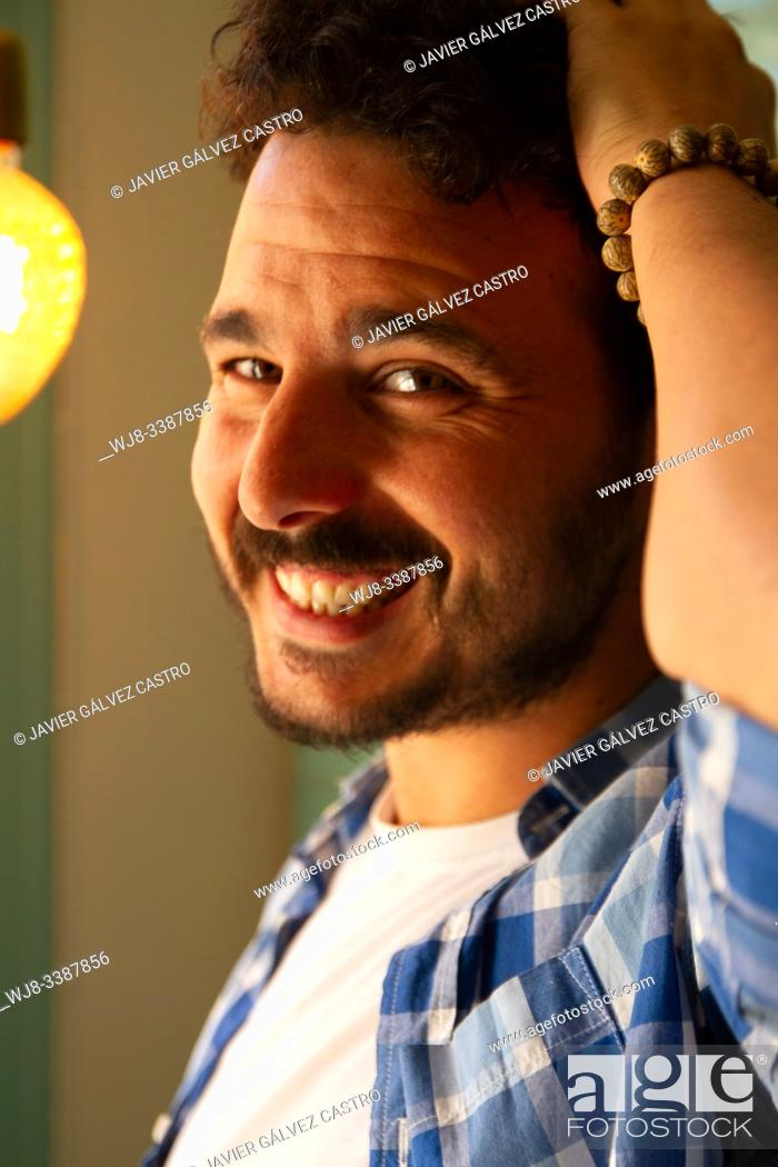 Stock Photo: young man with sensual look sticking his hair.