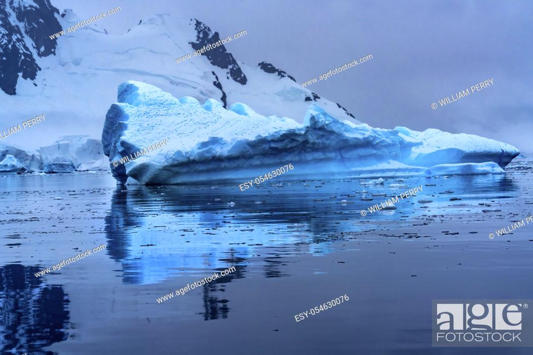 Stock Photo: Floating Blue Iceberg Reflection Snow Mountains Paradise Bay Skintorp Cove Antarctica. Glacier ice blue because air squeezed out of snow.