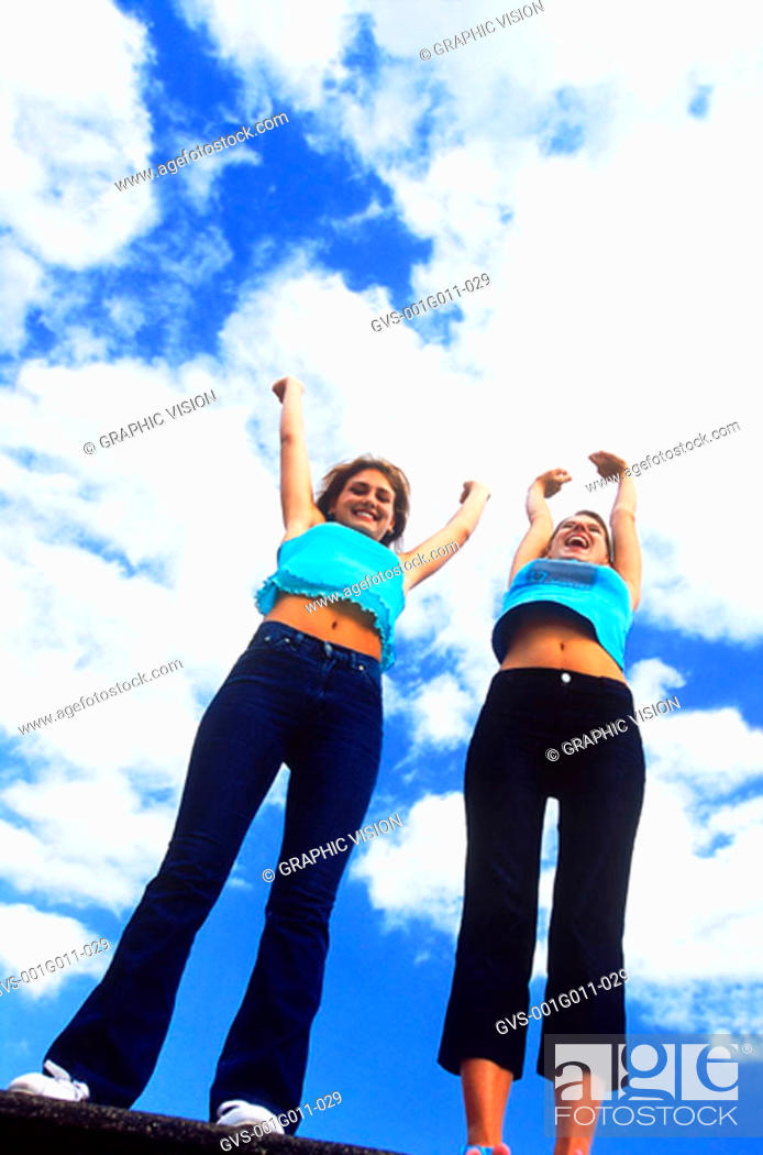 Stock Photo: Low angle view of young women standing with their arms raised.