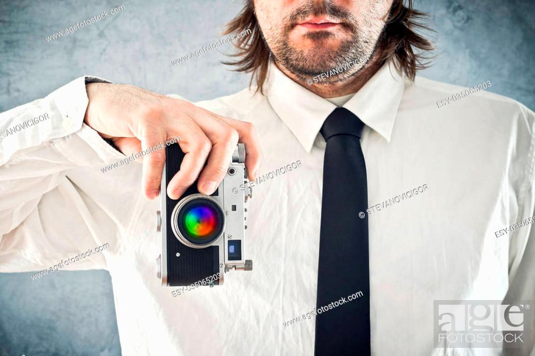 Stock Photo: Businessman taking picture with retro style photo camera.