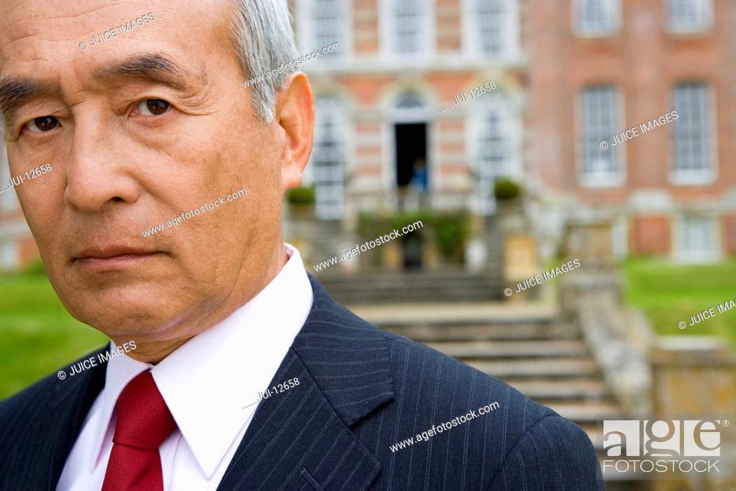 Stock Photo: Mature businessman by manor house, portrait, close-up.