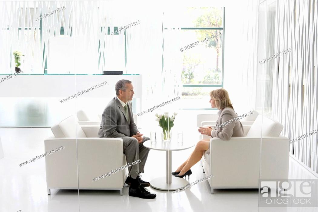 Stock Photo: Business people having meeting in office lobby.