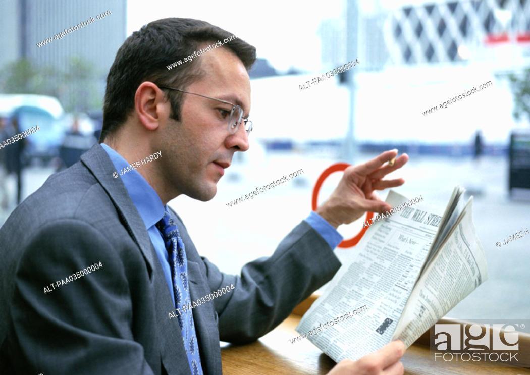 Stock Photo: Businessman reading newspaper.