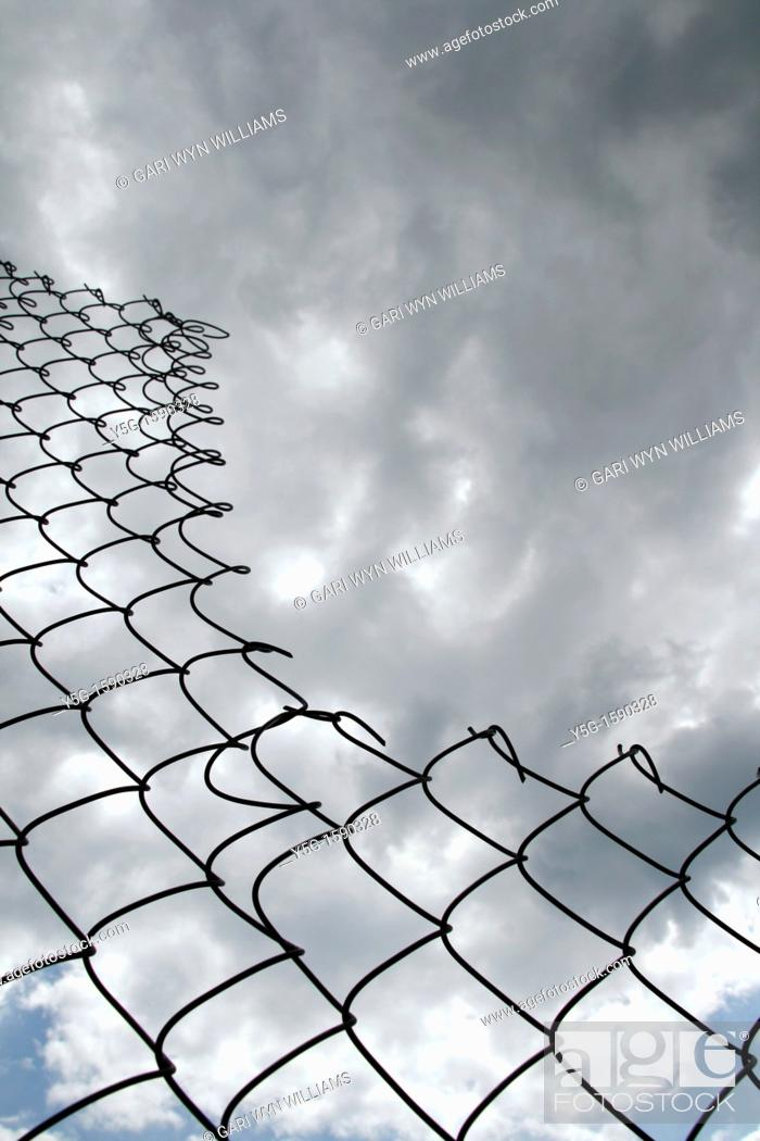 Stock Photo: close up of metal wire fence barrier and dark cloudy moody sky.