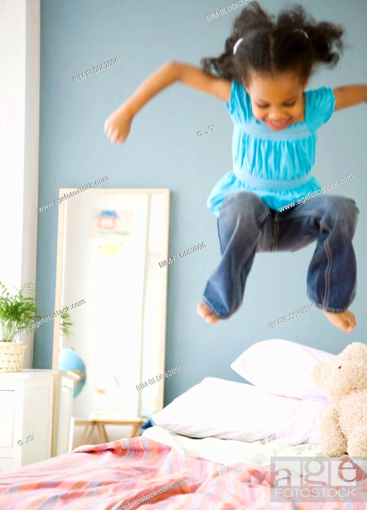 Stock Photo: Mixed race girl jumping on bed.