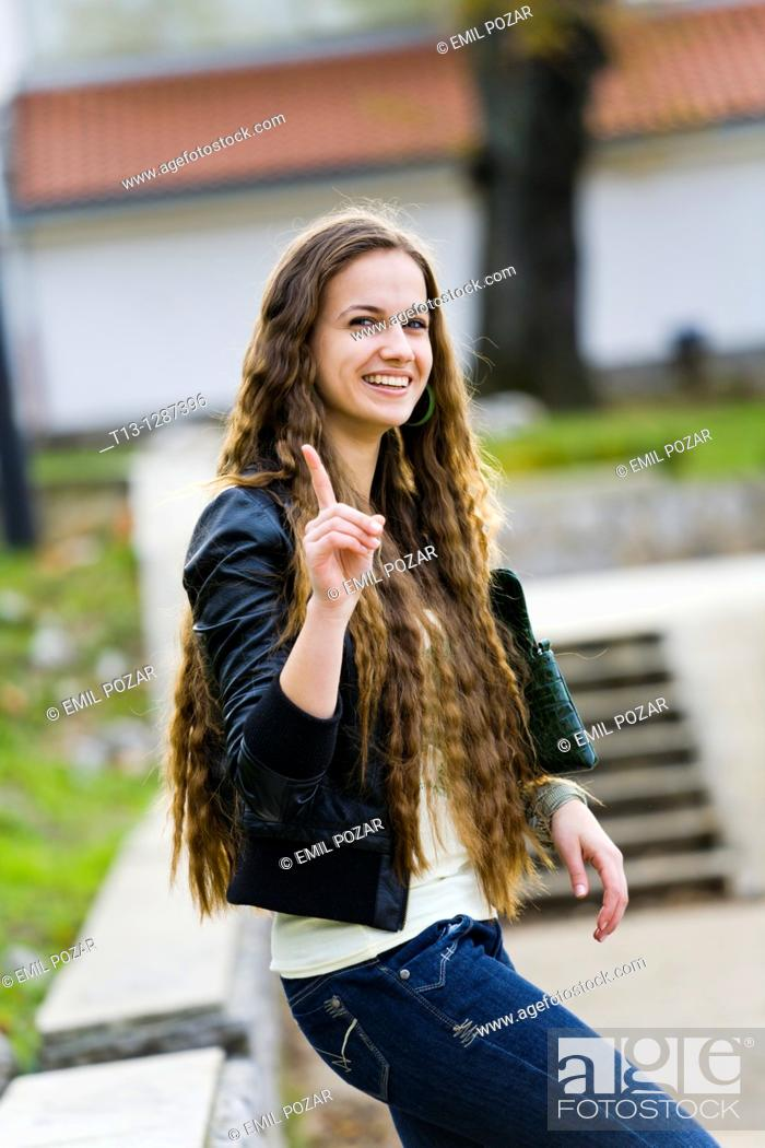 Stock Photo: Warning with a finger smiling young woman.