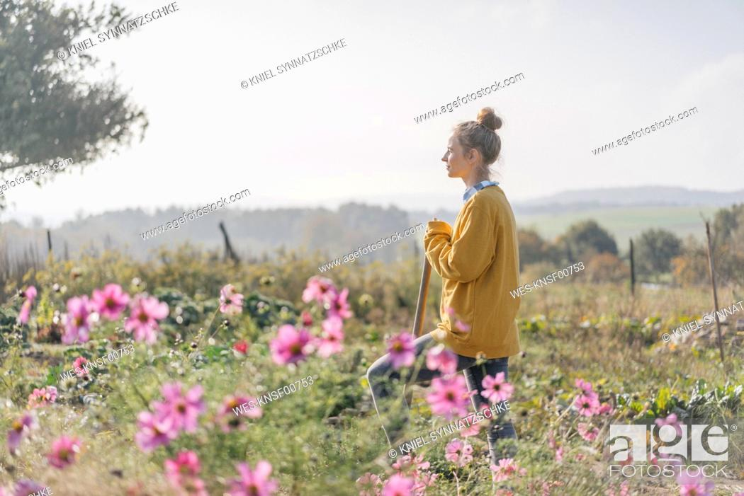 Stock Photo: Young woman with spade in cottage garden.