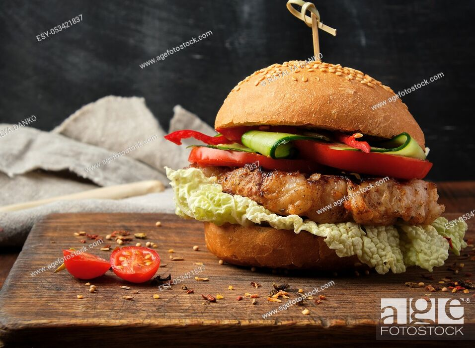 Stock Photo: homemade hamburger with pork fried steak, red tomatoes, fresh round bun with sesame seeds on a vintage brown wooden board.