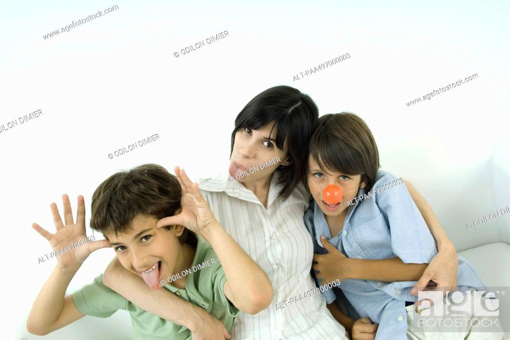 Stock Photo: Mother and two sons, sticking out their tongues, one wearing clown's nose.