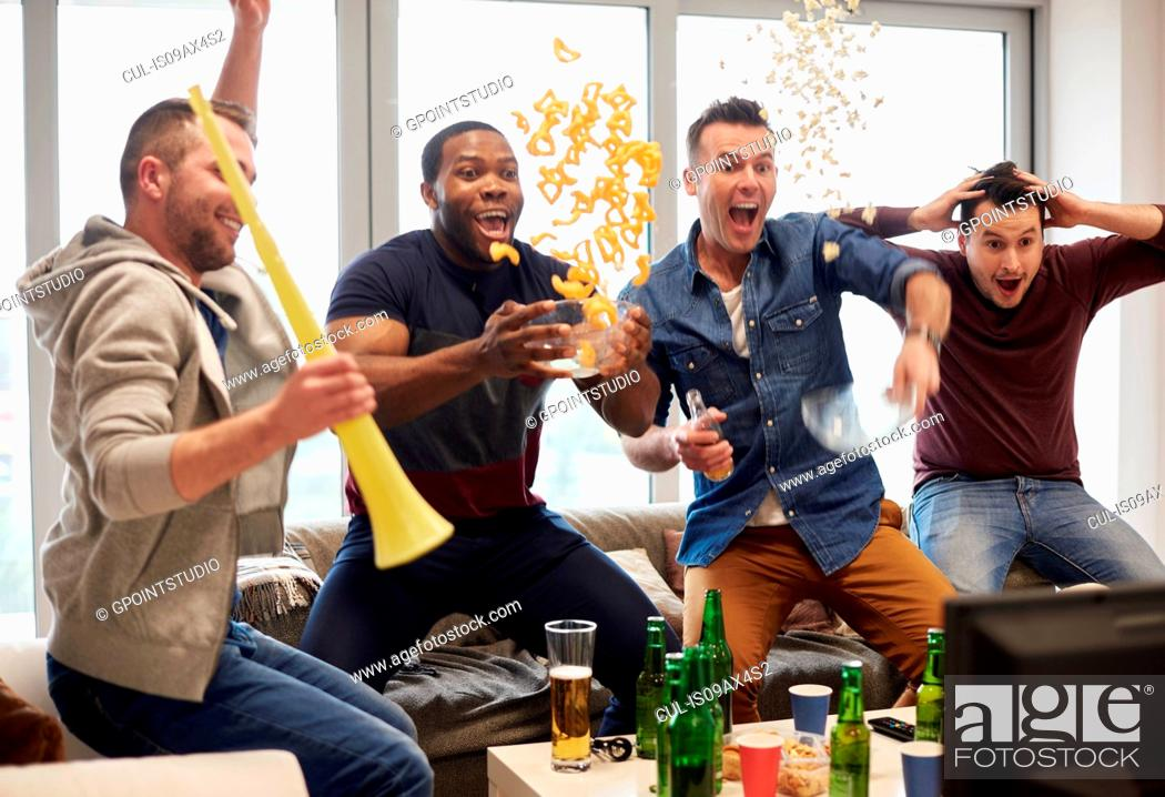 Imagen: Group of men watching sport event on television celebrating.