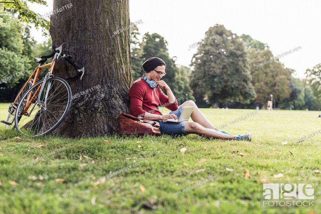 Imagen: Man using laptop in park.