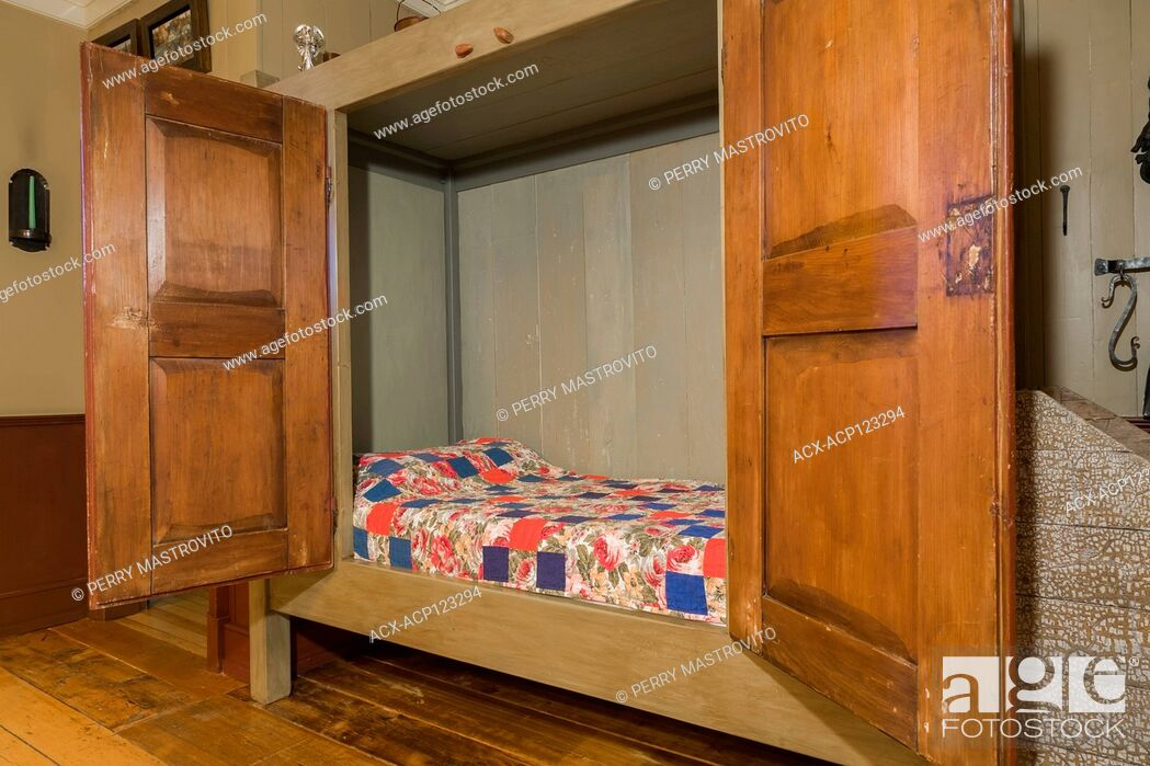 Stock Photo: Single bed hidden in an old wooden armoire in the dining room inside an old circa 1805 Canadiana cottage style home, Quebec, Canada.