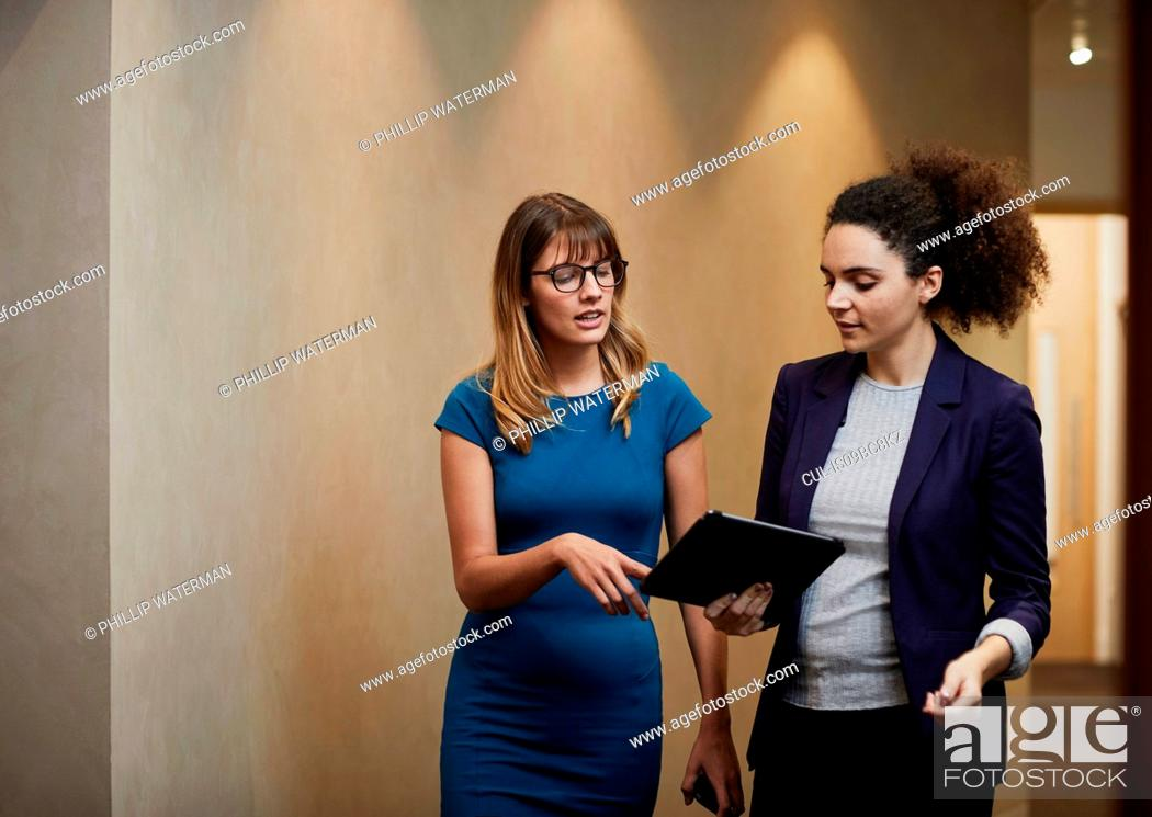 Photo de stock: Businesswomen walking and looking at digital tablet in office corridor.
